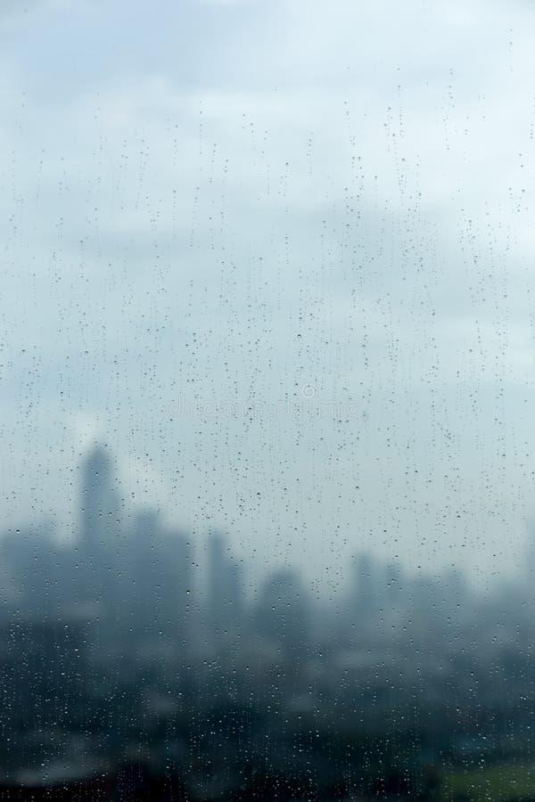 Gocce di pioggia sul vetro di finestra e paesaggio urbano e luce solare vaghi dentro immagini stock