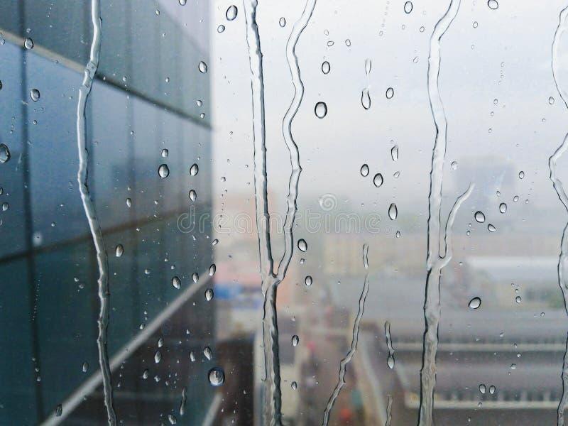 Gocce di pioggia sul vetro di finestra con la parete del grattacielo sui precedenti fotografia stock libera da diritti
