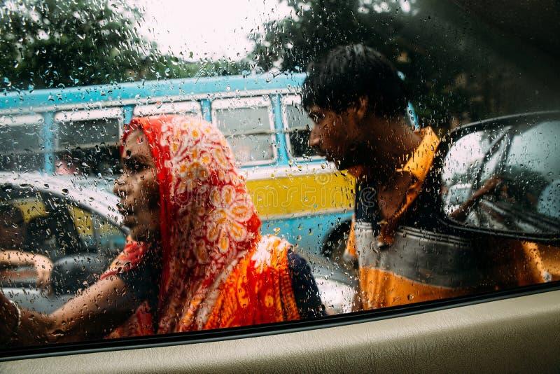 Gocce di pioggia sul vetro di finestra dell'automobile con il mendicante della sfuocatura, una donna anziana e un uomo fuori sull fotografie stock libere da diritti