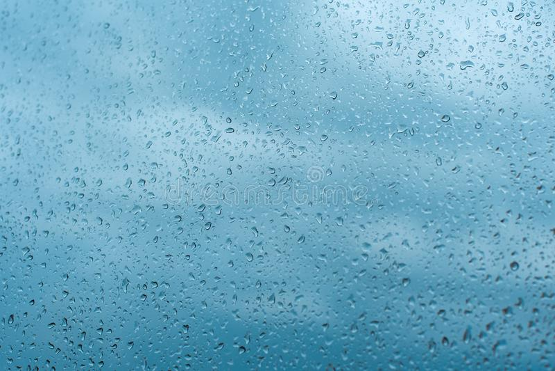 Gocce di pioggia sul vetro di finestra DOF basso E Fondo dell'acqua blu con le gocce di acqua immagini stock