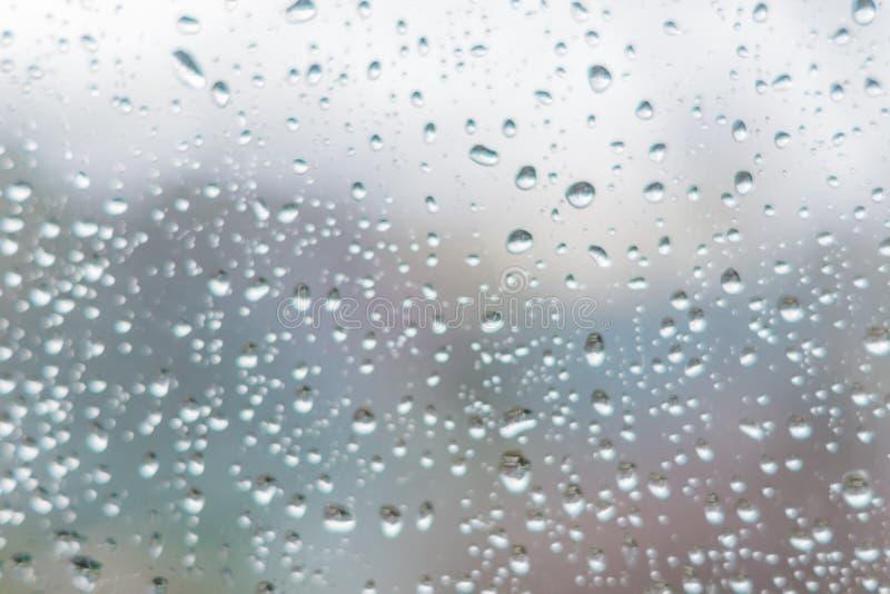 Gocce di pioggia sul vetro di finestra scuro Sottragga la struttura della priorità bassa d immagine stock