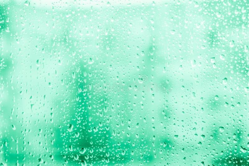 Gocce di pioggia sul vetro di finestra sui precedenti magici di colore della menta fotografia stock