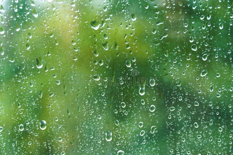 Gocce di pioggia sul vetro nel giorno di estate immagini stock libere da diritti