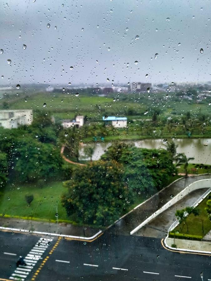 Gocce di pioggia sulla finestra con gli alberi e la strada verdi del catrame fotografia stock libera da diritti