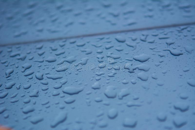 Gocce di pioggia sulla superficie dell'automobile, movente in pioggia, fondo di struttura fotografie stock libere da diritti