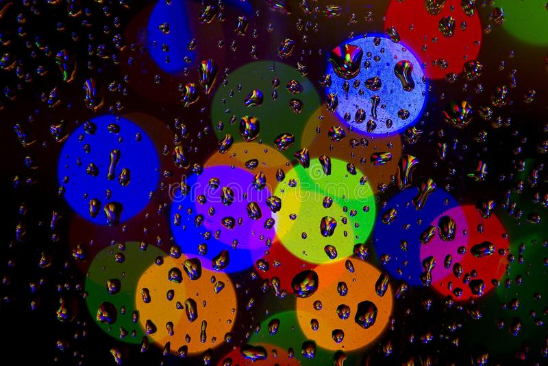 Gocce di pioggia variopinte e luci di colore immagini stock
