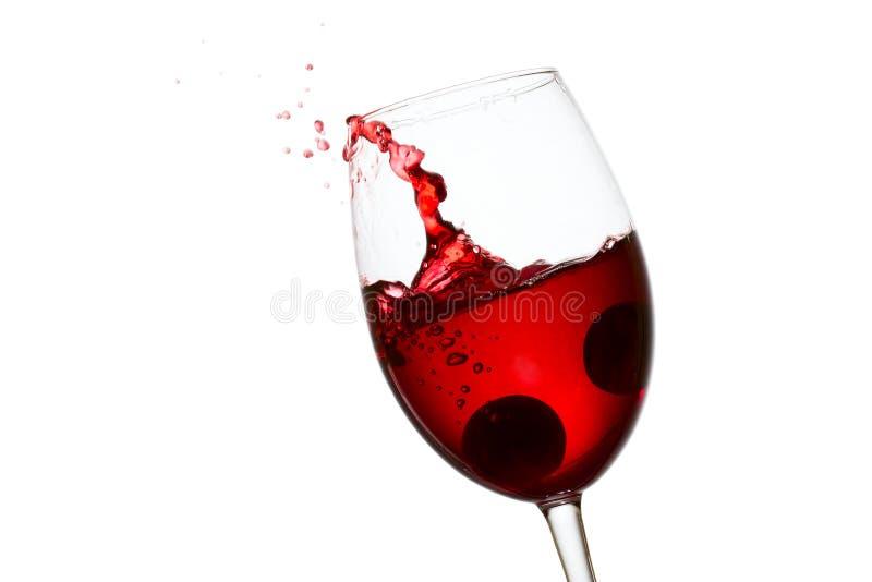 Gocce spettacolari di volo e della spruzzata di vino rosso in un vetro elegante fotografia stock
