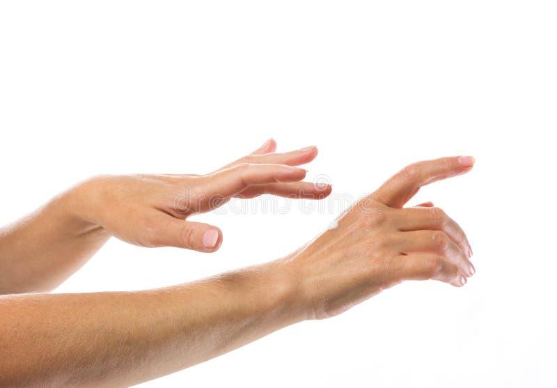 Goccia della crema sulla mano della donna fotografia stock