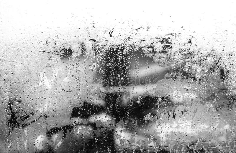 Goccia di acqua del fondo dell'estratto del parabrezza della via della citt? sulle luci e sulla pioggia di vetro Foto in bianco e immagini stock