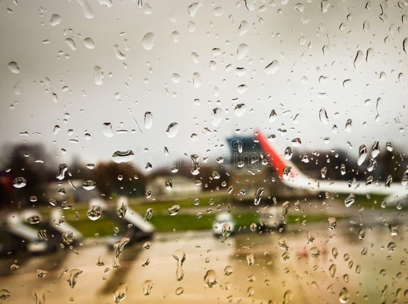 Goccia di acqua sulla finestra dello specchio dell'aeroplano fotografia stock