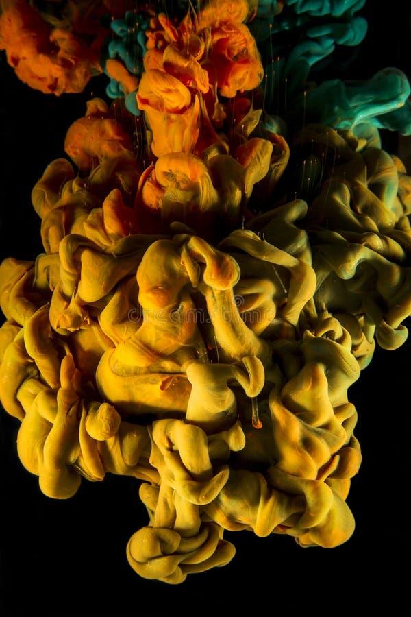 Goccia di colore inchiostro arancio, verde e giallo su fondo nero fotografie stock