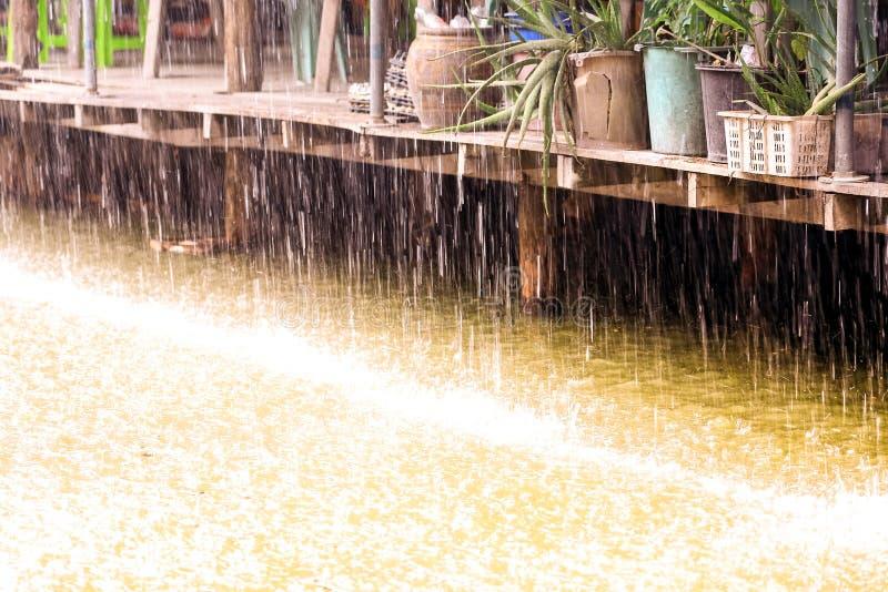 Goccia di pioggia nell'acqua con la casa di legno d'annata sul canale immagine stock
