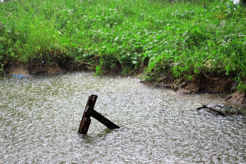 Goccia di pioggia nell'acqua con di legno d'annata in canale, come natura fotografia stock