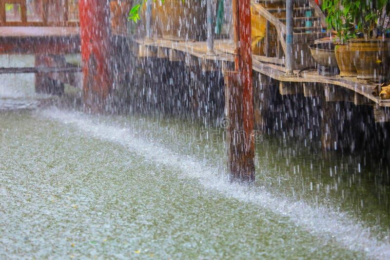 Goccia di pioggia pesante nell'acqua con la casa di legno d'annata sul canale fotografia stock