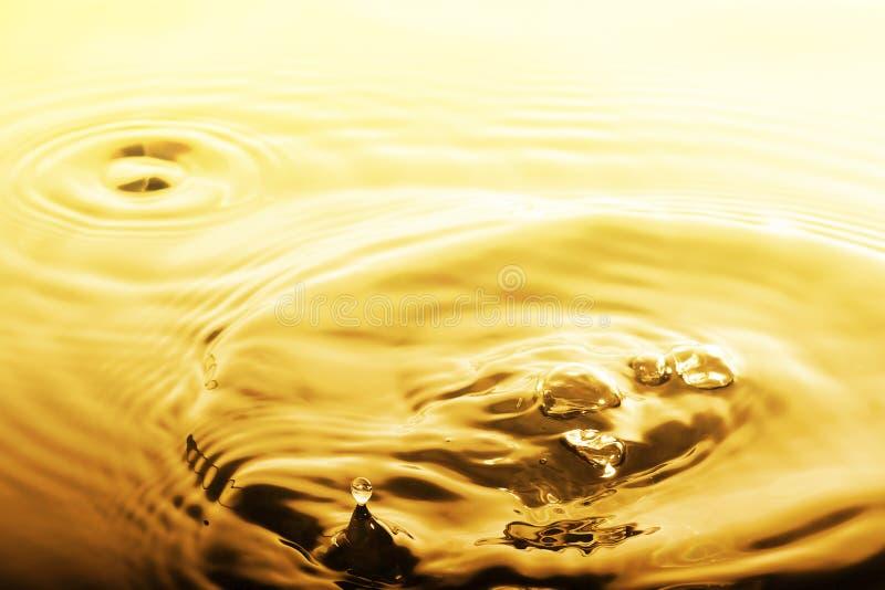 Goccia ed ondulazione liquide dell'oro fotografia stock libera da diritti