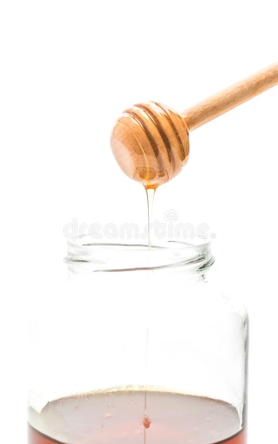 Gocciolamento del miele in barattolo immagini stock libere da diritti