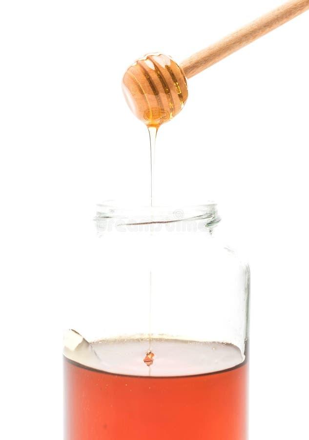 Gocciolamento del miele in barattolo fotografia stock