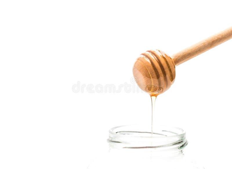 Gocciolamento del miele in barattolo fotografia stock libera da diritti