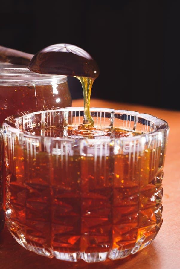 Gocciolamento del miele in barattolo su buio fotografia stock libera da diritti
