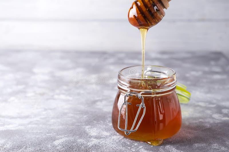 Gocciolamento del miele in barattolo sulla tavola fotografia stock libera da diritti