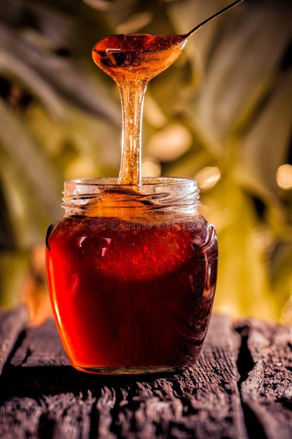 Gocciolamento del miele in barattolo sulla tavola fotografie stock libere da diritti