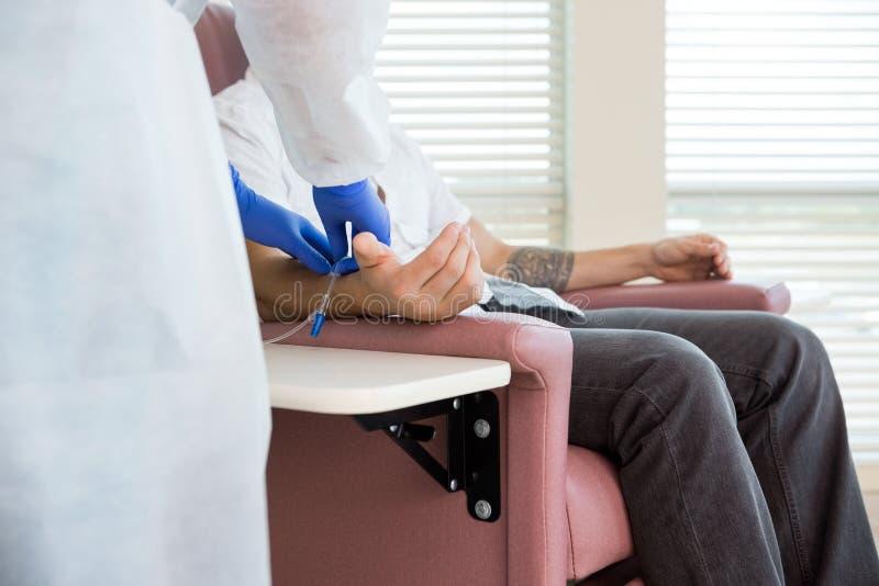 Gocciolamento di Adjusting IV dell'infermiere sulla mano del paziente nel Chemo immagine stock libera da diritti