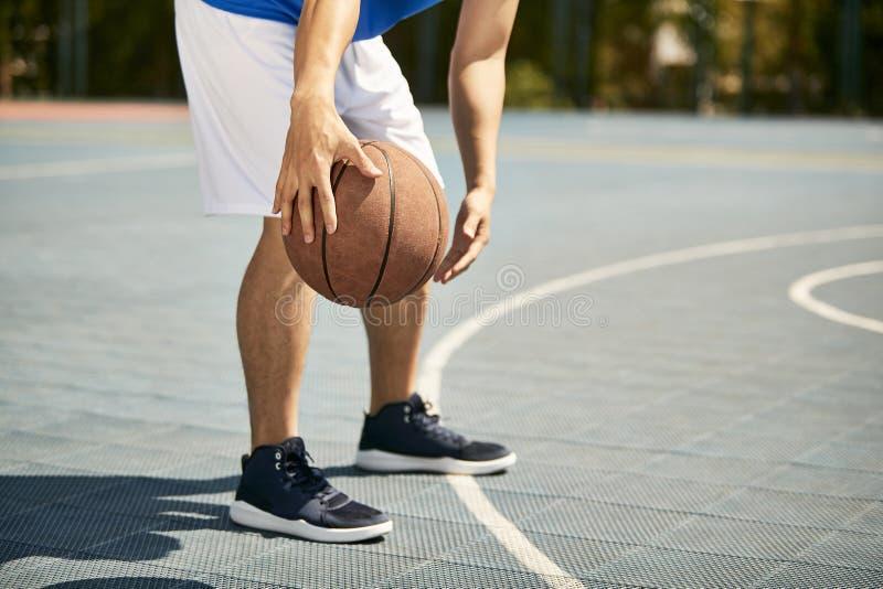 Gocciolamento di pratica del giovane giocatore di pallacanestro maschio asiatico immagine stock libera da diritti