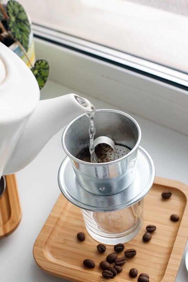 Gocciolamento, facendo, acqua di versamento sopra caffè macinato contenuto in filtro vietnamita da Phin su windowsiil Fuoco selet fotografie stock libere da diritti
