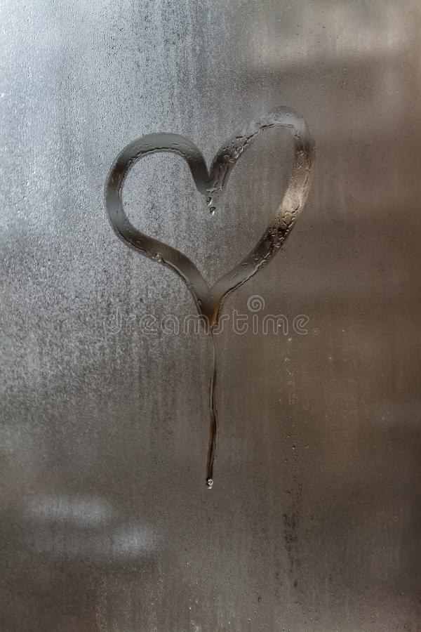 Gocciolamento sotto forma di un cuore su un finestra-vetro appannato Primo piano Fondo immagini stock