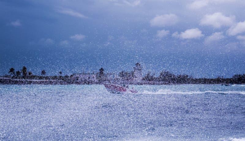 Goccioline davanti ad una piccola barca che supera velocemente la superficie dell'acqua immagini stock