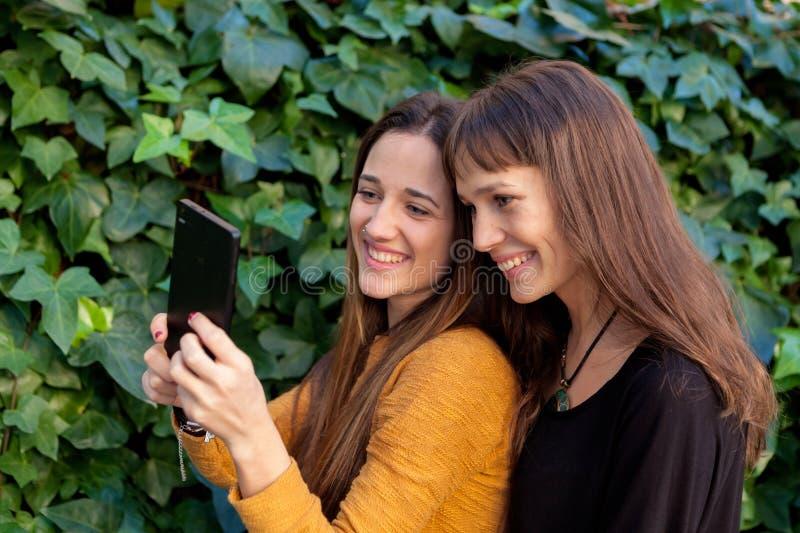 Goce de dos hermanas de un día con un móvil imagen de archivo