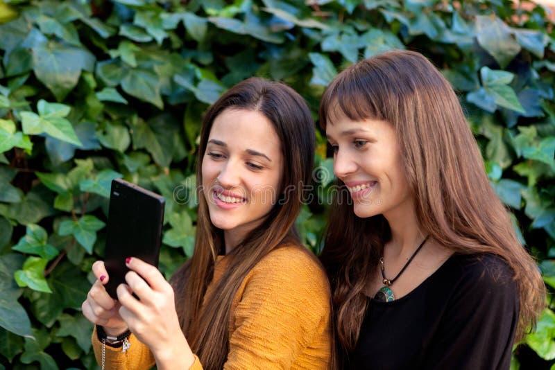 Goce de dos hermanas de un día con un móvil imagen de archivo libre de regalías