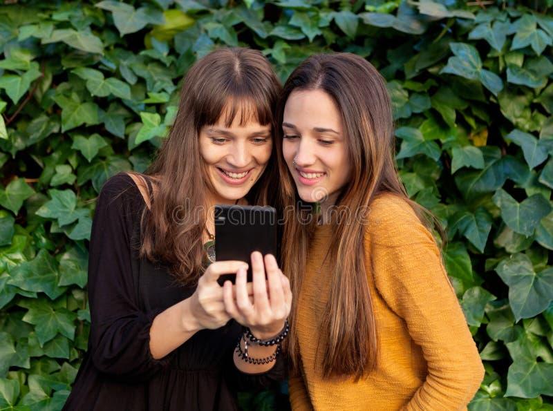 Goce de dos hermanas de un día con un móvil fotos de archivo libres de regalías