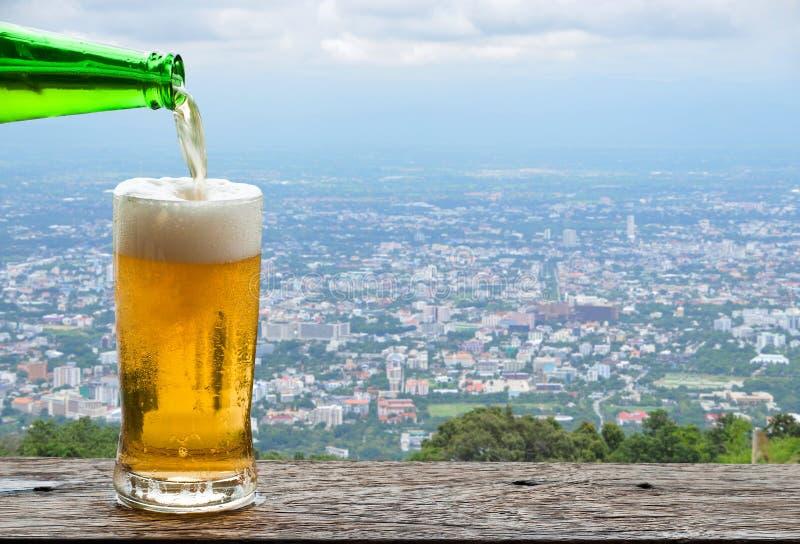 Goce de la cerveza con paisaje urbano urbano imagen de archivo libre de regalías