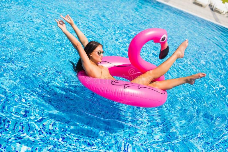 Goce de la chica joven de las vacaciones con las gafas de sol en la piscina foto de archivo