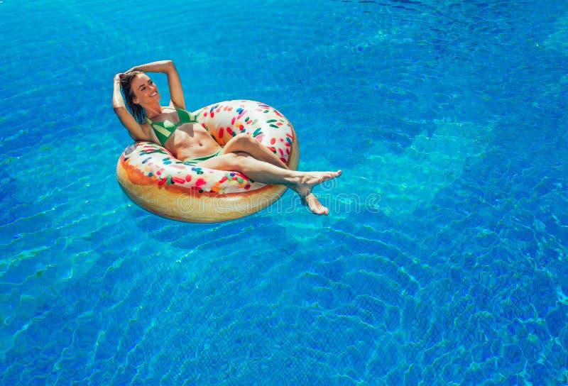 Goce de la mujer del bronceado en bikini en el colchón inflable fotografía de archivo