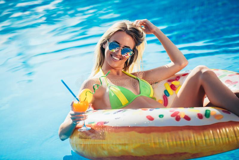 Goce de la mujer del bronceado en bikini en el colchón inflable en la piscina imágenes de archivo libres de regalías