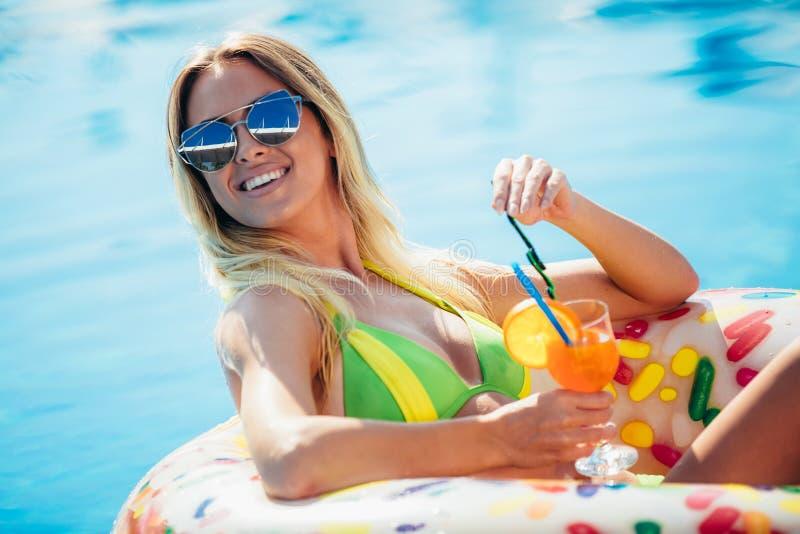 Goce de la mujer del bronceado en bikini en el colchón inflable en la piscina fotos de archivo libres de regalías