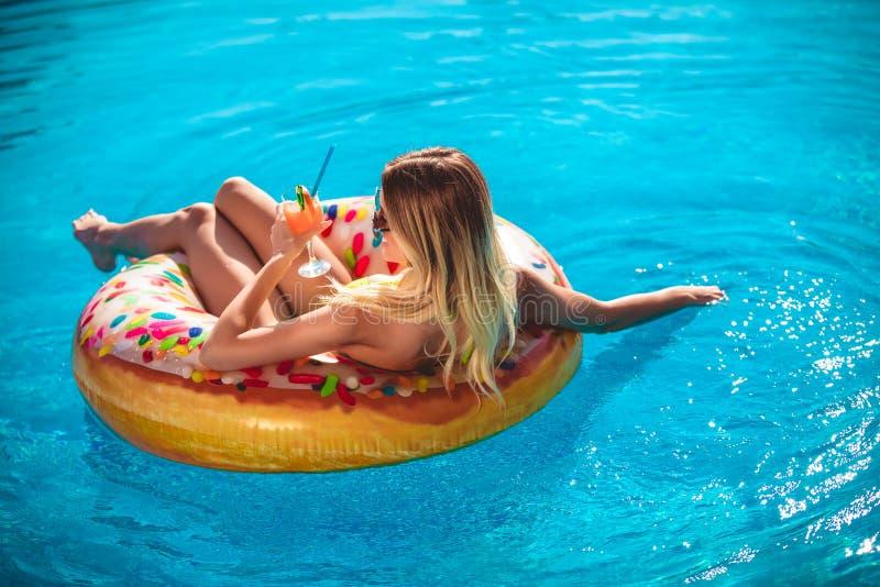 Goce de la mujer del bronceado en bikini en el colch?n inflable en la piscina imagen de archivo libre de regalías