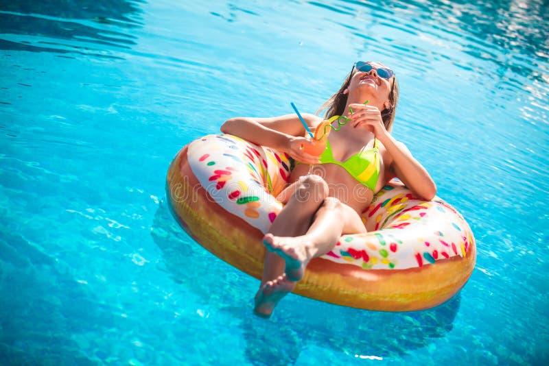 Goce de la mujer del bronceado en bikini en el colch?n inflable en la piscina imagen de archivo