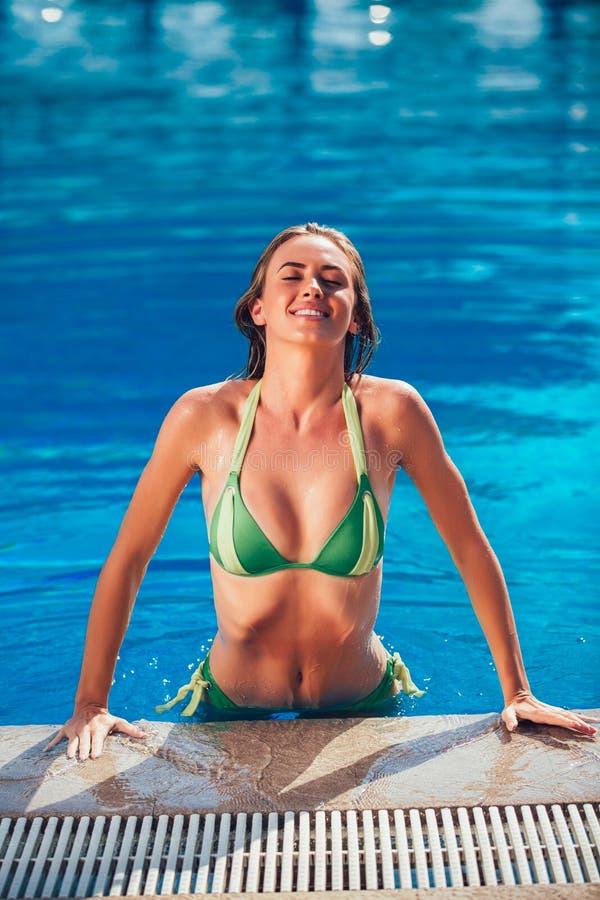Goce de la mujer del bronceado en bikini en la piscina imágenes de archivo libres de regalías