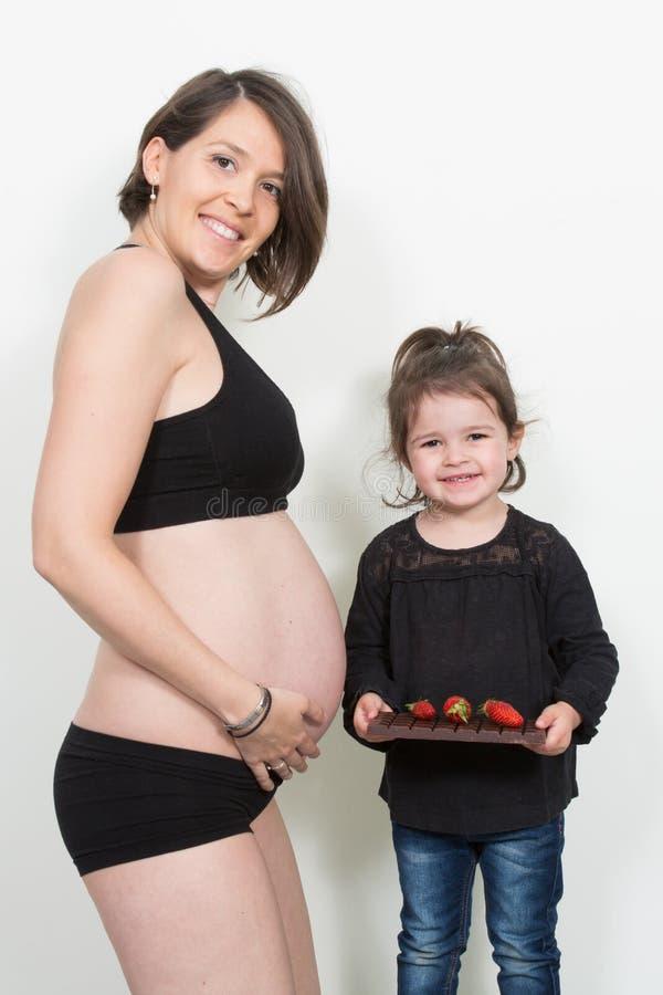 Goce de la mujer embarazada de comer el chocolate y la fresa en casa imagen de archivo libre de regalías