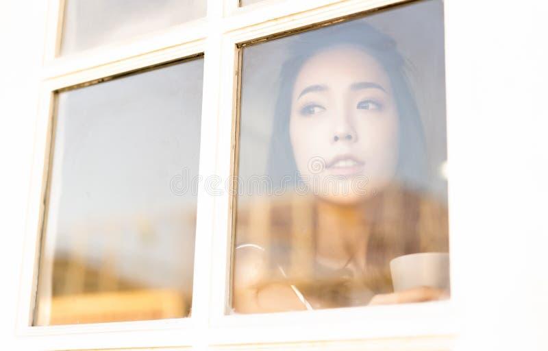 Goce de su caf? fresco Retrato del caf? de consumici?n de la mujer asi?tica joven hermosa por la ma?ana y de la mirada con rato d imagen de archivo libre de regalías