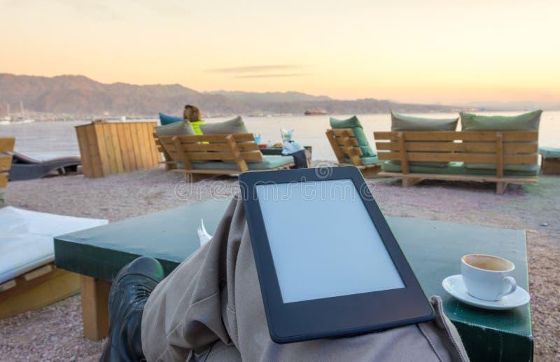 Goce de un e-lector del eBook en la playa foto de archivo libre de regalías