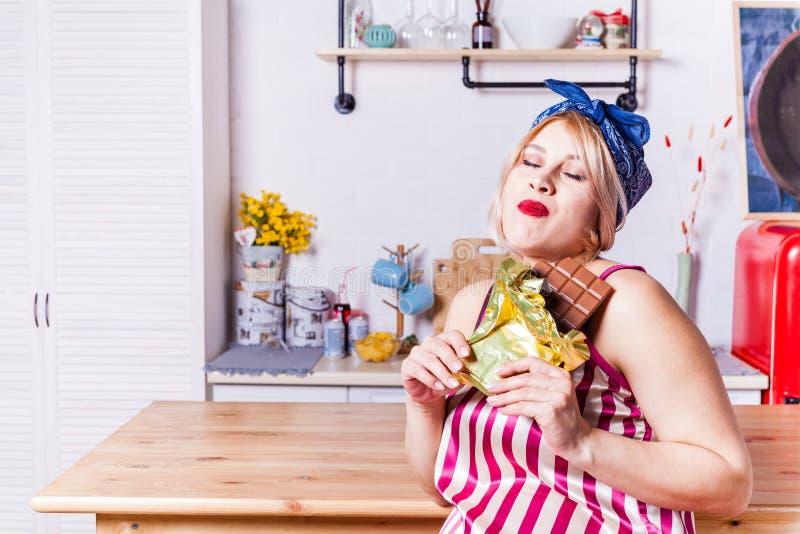 Goce embarazada de la mujer adulta de comer la barra de chocolate, espacio de la copia Rubios expectantes quieren algún encanto C foto de archivo libre de regalías