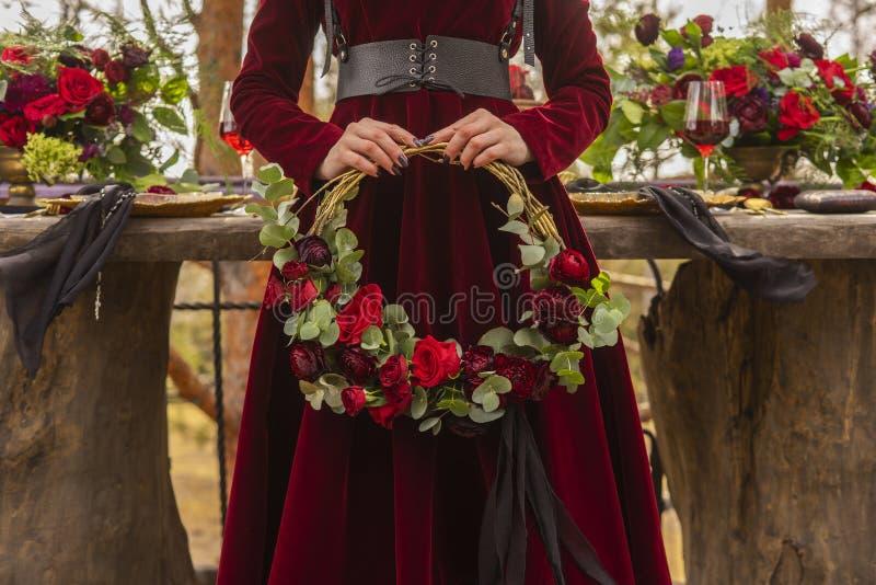 Gocka dziewczyny panna młoda jest ubranym czerwoną brokat suknię trzyma wianek obrazy stock