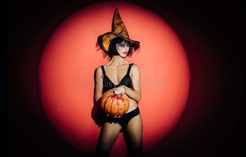 Gocka kobieta w czarownicy Halloween kostiumu z Halloween kapeluszową pozycją nad czerwonym nocy światła tłem Piękny nagi zdjęcia royalty free