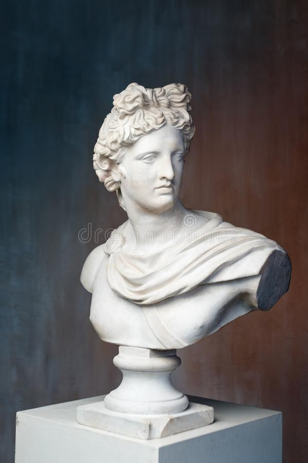 Free God Apollo Bust Sculpture. Ancient Greek God Of Sun And Poetry Plaster Copy Of A Marble Statue On Grange Concrete Wall Stock Photos - 140500573