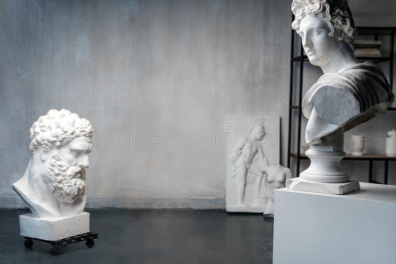 God Apollo bust sculpture and bust of the Farnese Hercules. Head sculpture, plaster copy of a marble statues of Greek. Gods and heroes on grange concrete wall royalty free stock photography