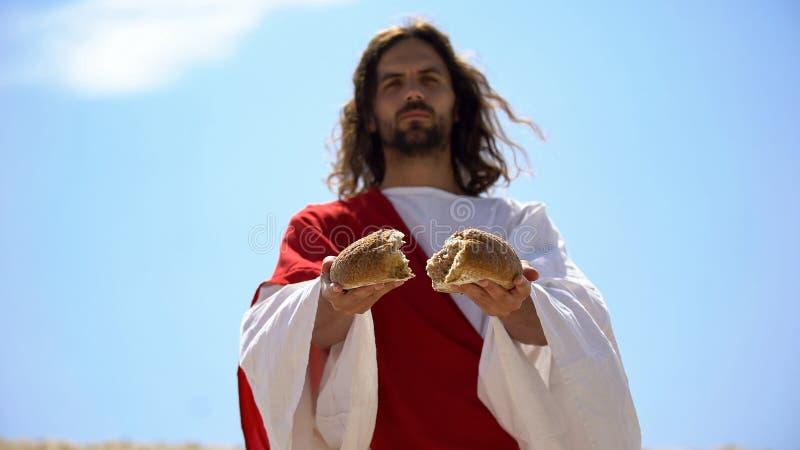God breekt brood in twee gelijke delen, het concept van gerechtigheid, liefdadigheid om honger te voeden royalty-vrije stock fotografie